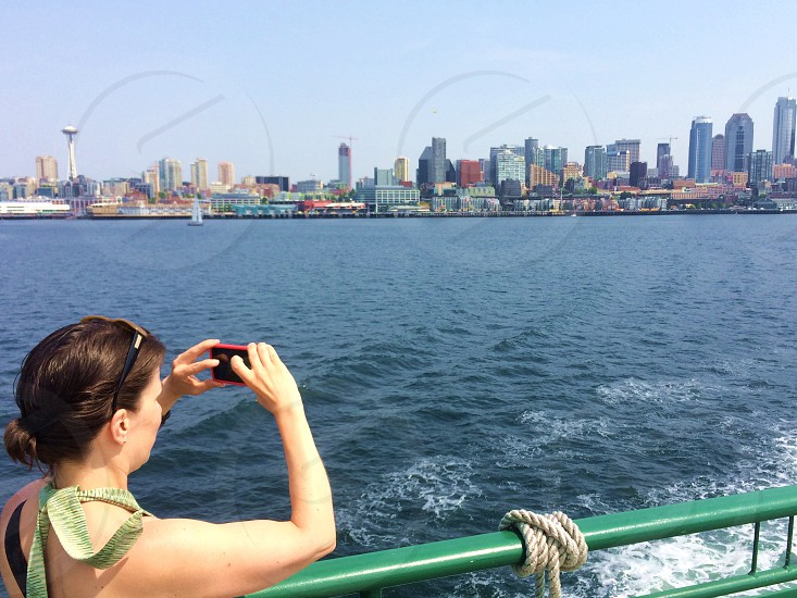 Subject taking photo with smartphone. Seattle from ferry landscape cityscape. photo