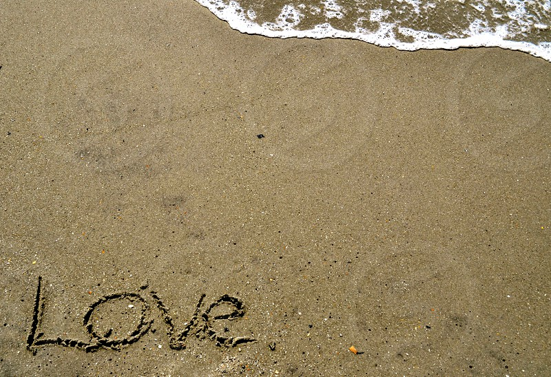 Love written in the sand with wave photo