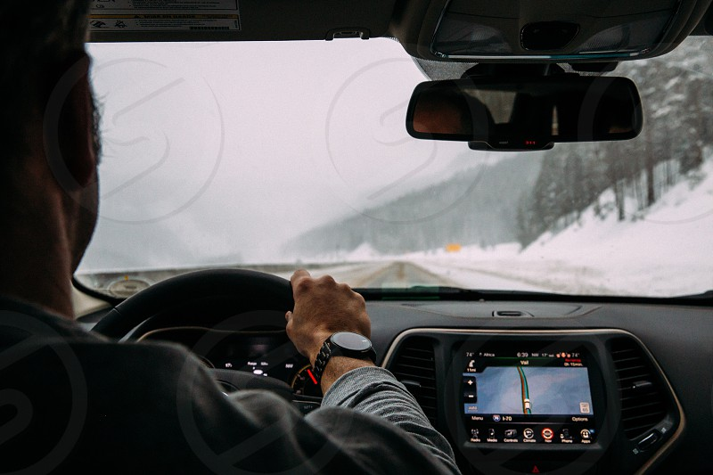 man driving on snowy road during day photo