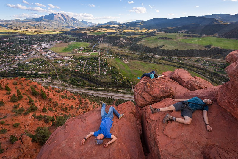 3 persons lying on brown rocky mountain top with overlooking view of the town at daytime photo