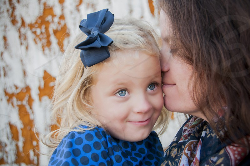 smiling woman kissing smiling girl with blue ribbon on her hair photo
