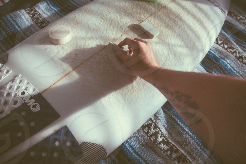 person waxing white snowboard photo