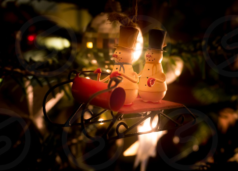 Traditional Christmas tree decoration two snowmen in top hats on a sleigh photo