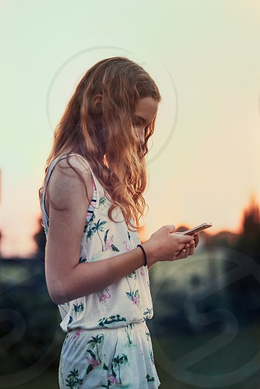 Young woman using mobile phone smartphone standing in a backyard photo