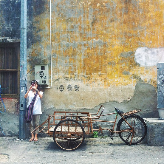 woman wearing white shirt beside tricycle photo