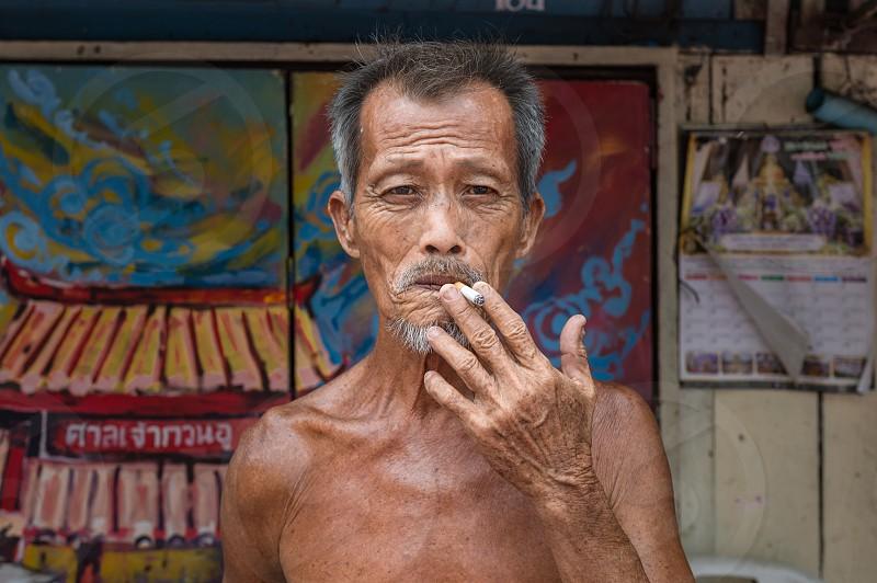 Elderly Thai man smoking cigarette in Bangkok Thailand.  photo