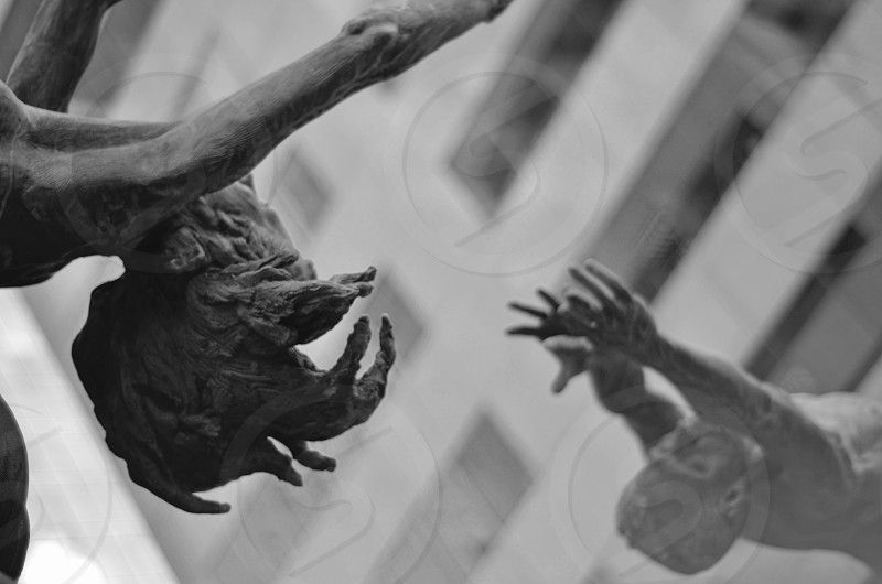 grayscale photography of man rise his hand photo