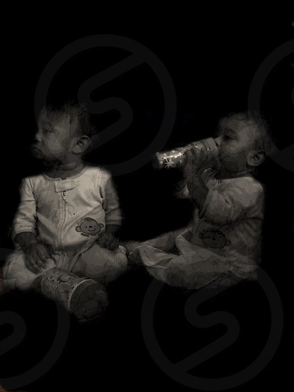 grayscale photography of two toddlers in white footies photo