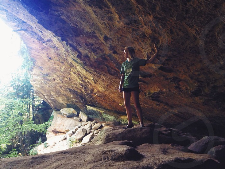 woman wearing green shirt under brown rock cave photo