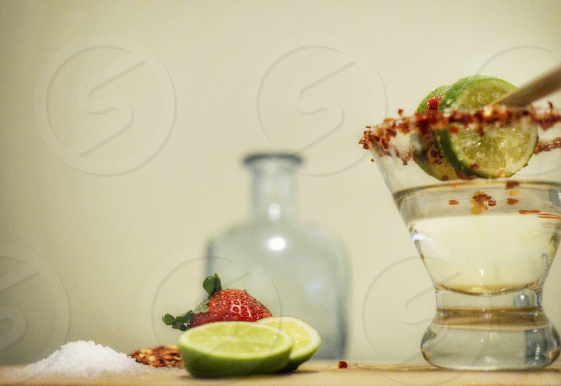 2 lime slice and strawberry beside tequila on shot glass photo