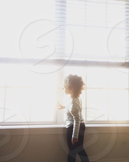 girl standing front of window photo