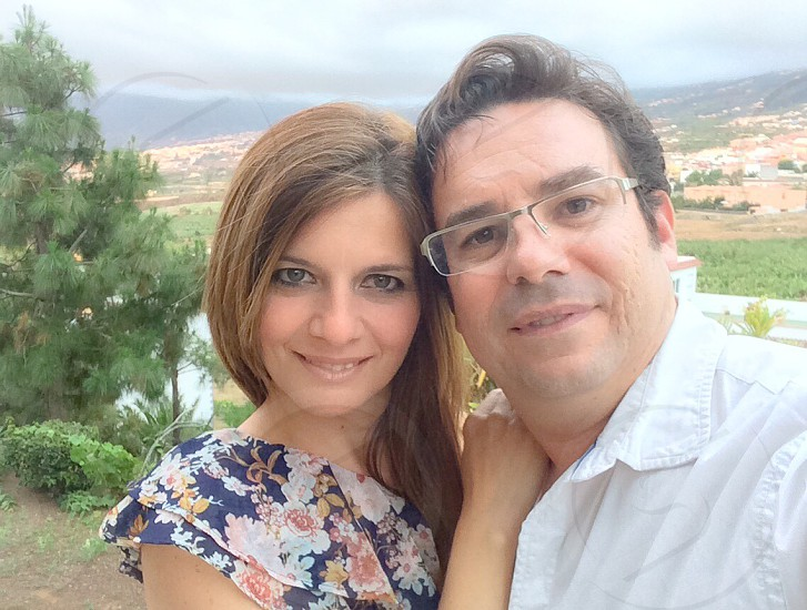man wearing white dress shirt and woman wearing blue and white floral top taking selfie photo