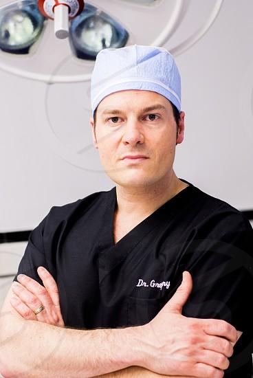man in black v neck medical scrubs wearing blue disposable hat photo
