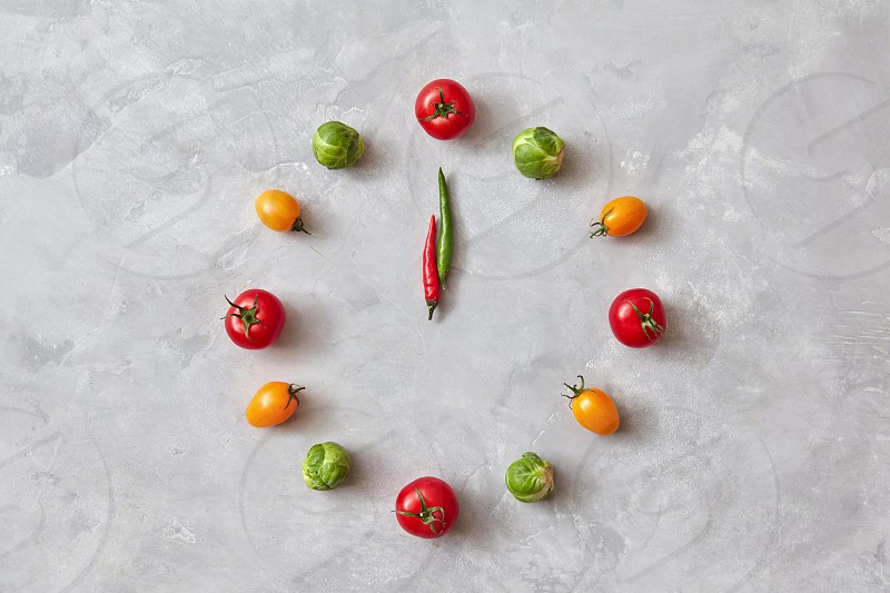 Vegetable clock from colorful cherry tomatoes carrots brussels cabbage and moving arrows from chili peppers on a gray stone background. Flat lay. photo