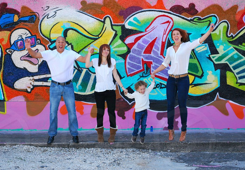 Family having fun jumping off of a curb in front of a graffiti wall photo