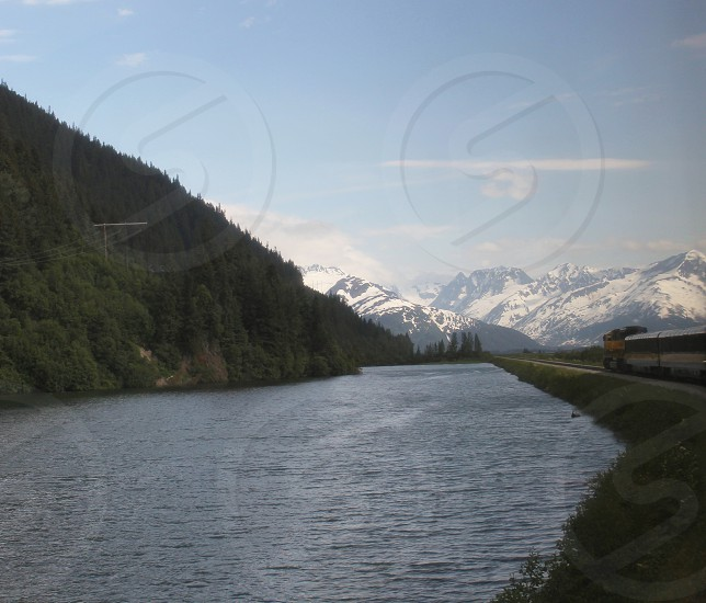 Train past the mountains and lake in Alaska photo