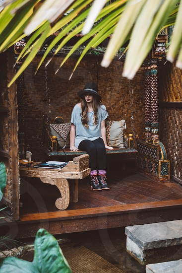 woman wearing gray scoop neck shirt and black leggings with black fedora hat and black leather shoes sitting on sofa in gazebo photo