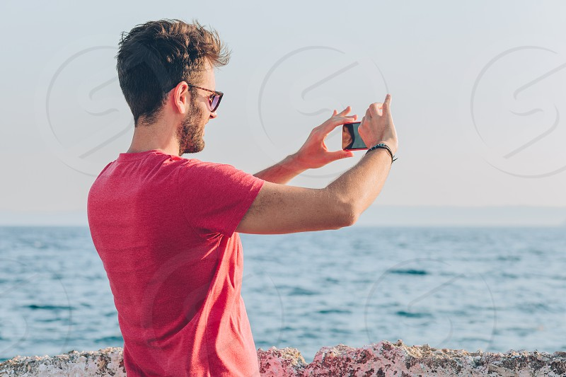 Young man tourist taking photo with smartphone by the sea photo