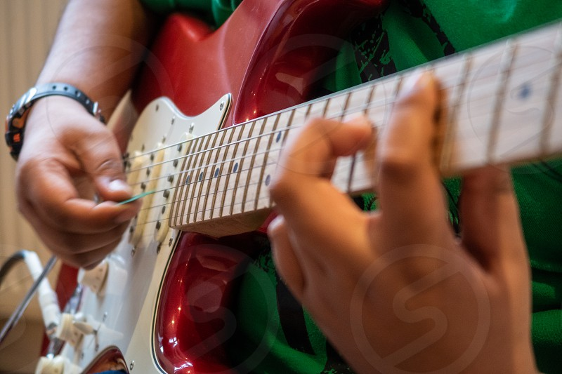 music musician guitar electric playing practising practicing sound child boy learning play young close up hands plectrum strumming photo
