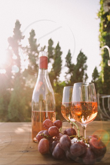 two wine glasses filled with rose wine on a table next to the bottle and purple table grapes surrounded by trees under the sun photo