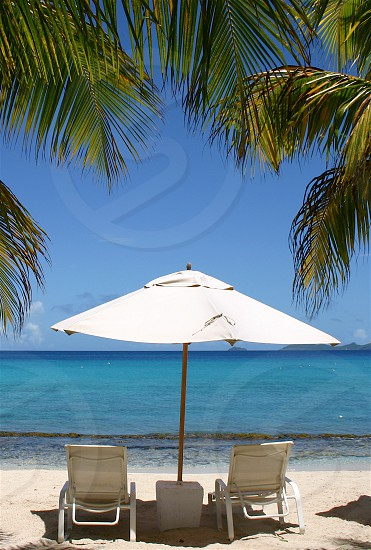 Beach umbrella with two empty chairs overlooking the beautiful Caribbean sea.  Framed by palm trees photo