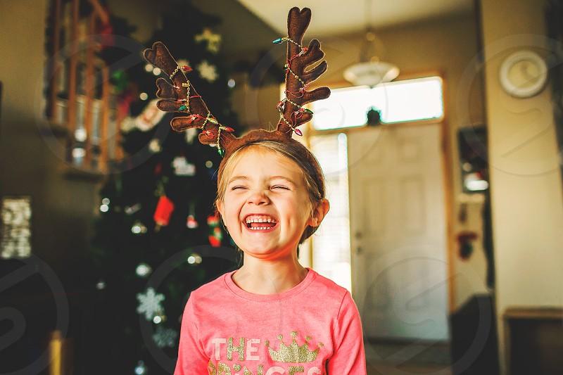 Christmas girl wearing reindeer antlers and laughing photo