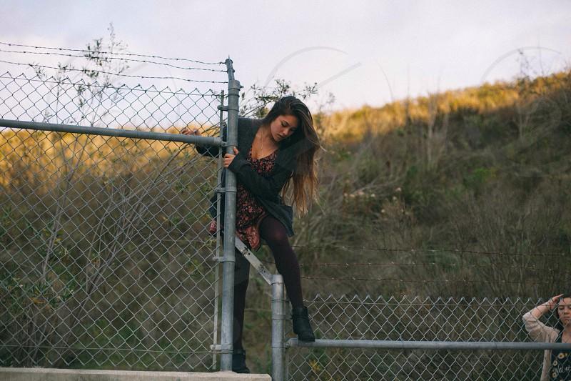 woman wearing black cardigan climbing fence photo