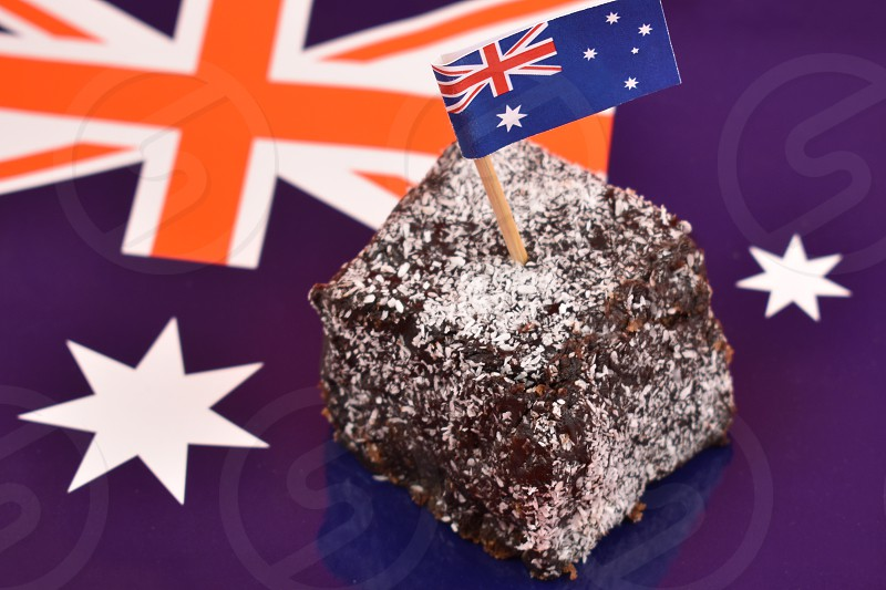 Lamington and Australian flag. Lamington on a national background. Australian sweet delicacy. Important day. Lamington Day background. Australian cake with flag photo