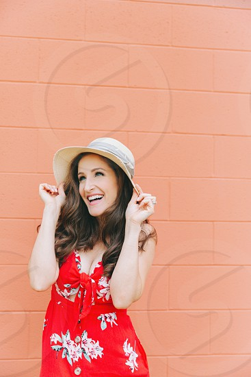 A portrait of a beautiful young woman wearing a hat against an orange wall.  photo