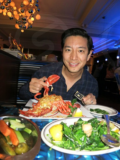 man smiling and holding lobster photo