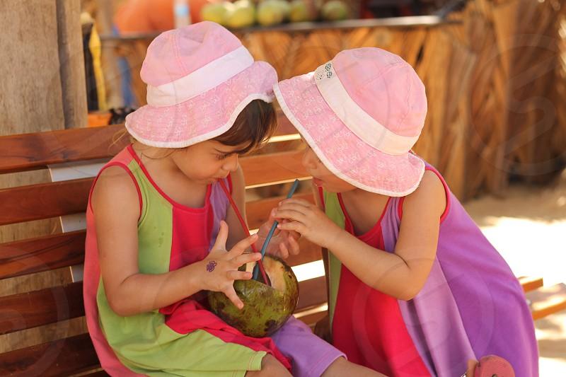 twins sharing coconut juice photo