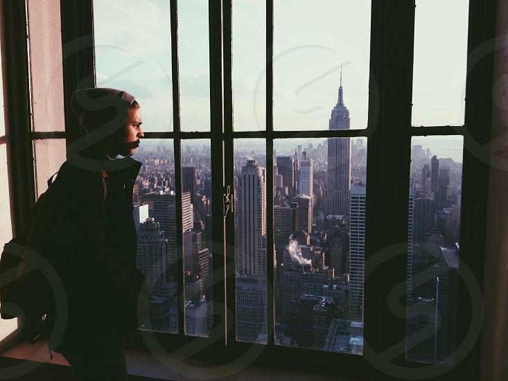 man in black jacket standing near glass window photo