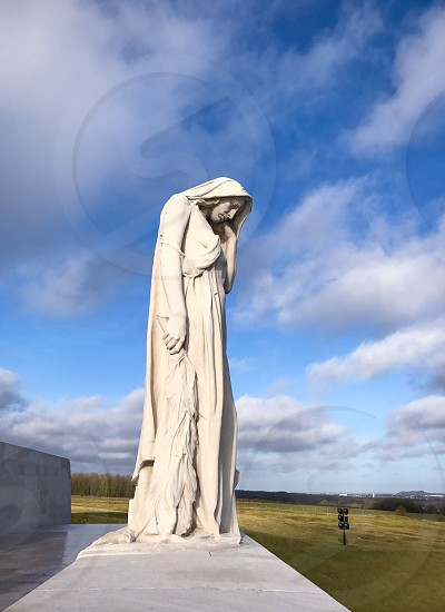 Outdoor day vertical portrait colour Vimy Ridge France Europe European Battle of Arras Western Front World War One WWI WW1 First World War battleground war warfare trench Trenches memorial remembrance commemoration white marble stone carved Canada Canadian mourning monument sky clouds blue figure Statue mother crying weeping photo