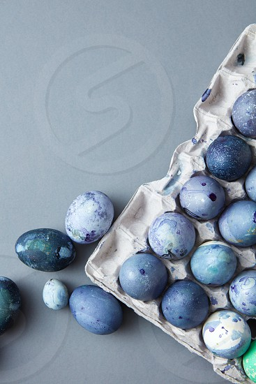Colorful Easter eggs in a box on gray background with copy space flat lay photo