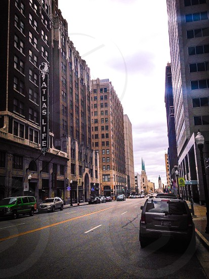 city street under white and gray clouds photo