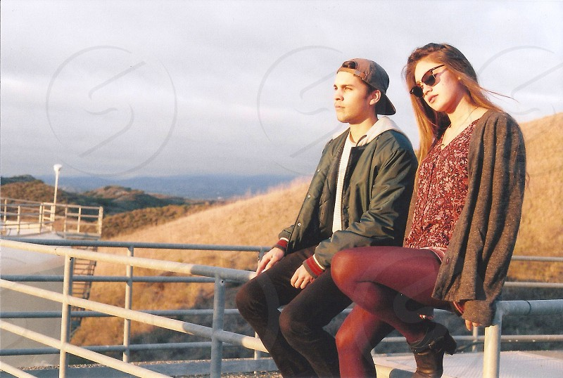 man and woman sitting on a white metal railing photo