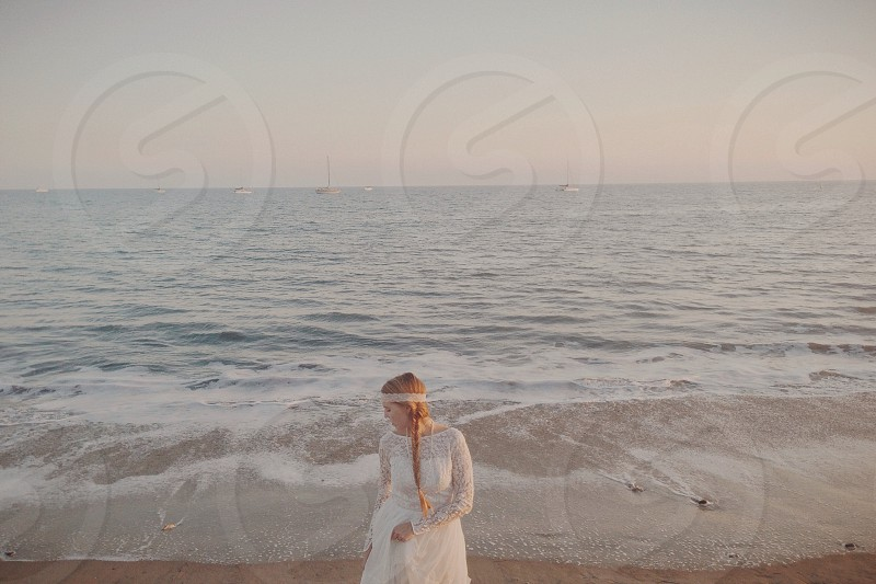 woman in white lace gown on the beach photo