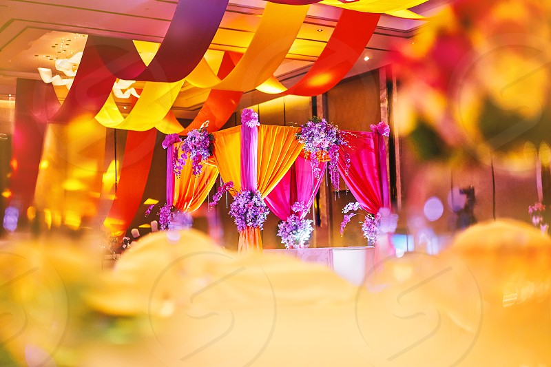 Selective focus on the colorful stage decoration with bright shade of color for bride and groom in the sangeet night of traditional indian wedding party celebration with blurry foreground photo