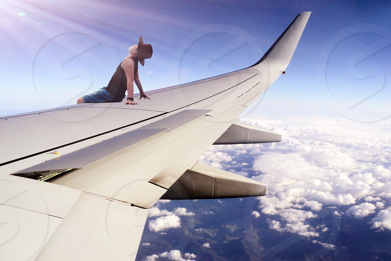 person sitting on the commercial plane wing facing the sky illustration photo