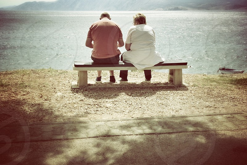 man and woman sitting fronting ocean photo