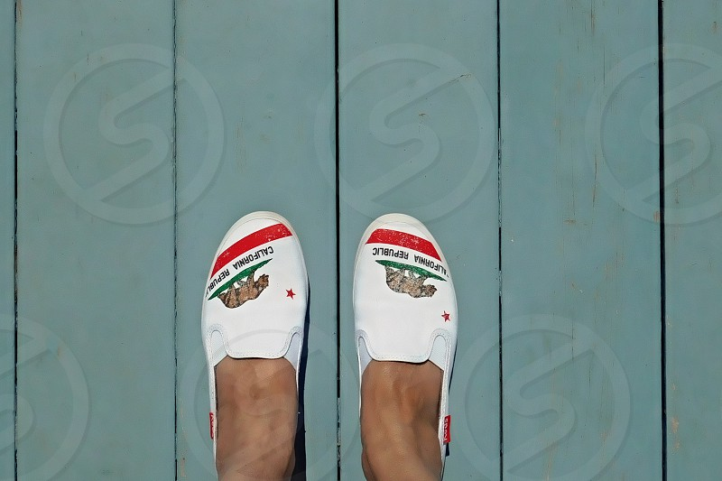 Looking down at white shoes with the California bear logo photo