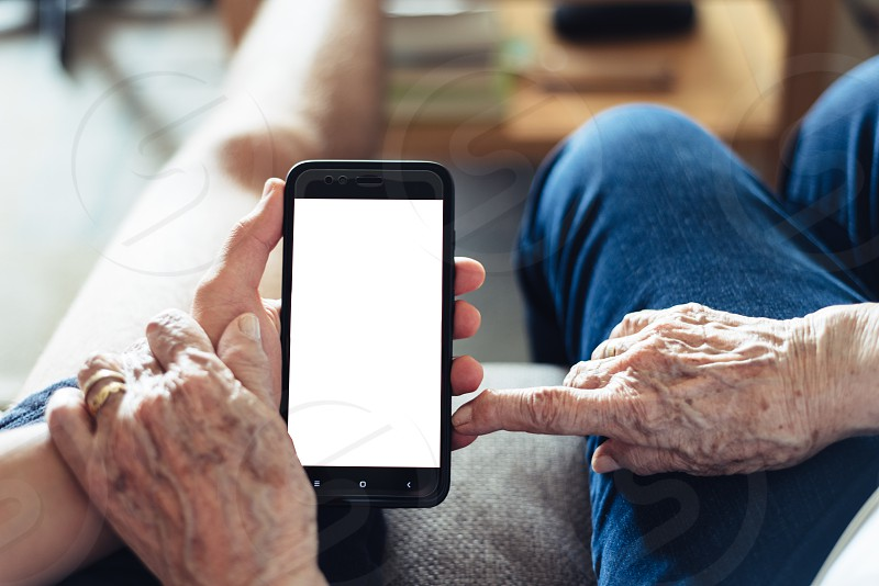 Close up of millennial showing smartphone to old woman photo