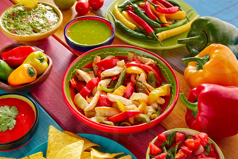 Chicken fajitas with mexican food guacamole pico de gallo chili peppers sauce and nachos photo