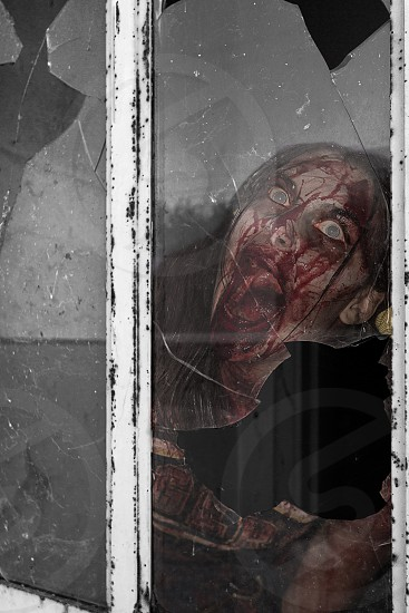 zombie woman full of red blood stains behind broken glass photo