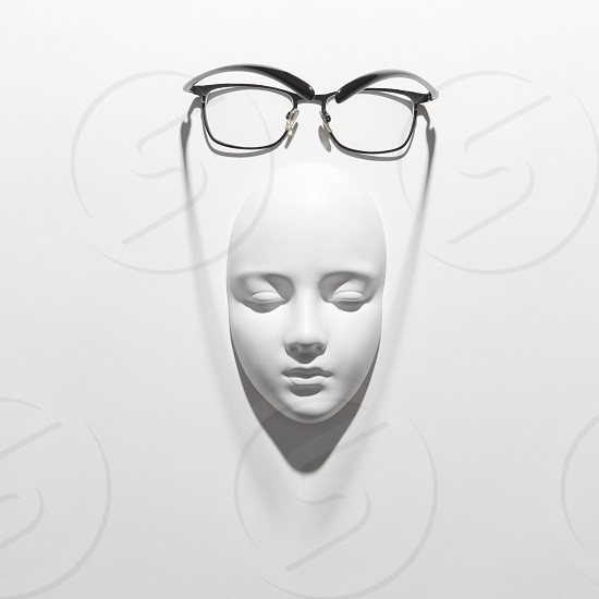 Stylish glasses with black frame or reading daily life on a gypsum face sculpture on a white background soft long shadows place for text. Flat lay photo