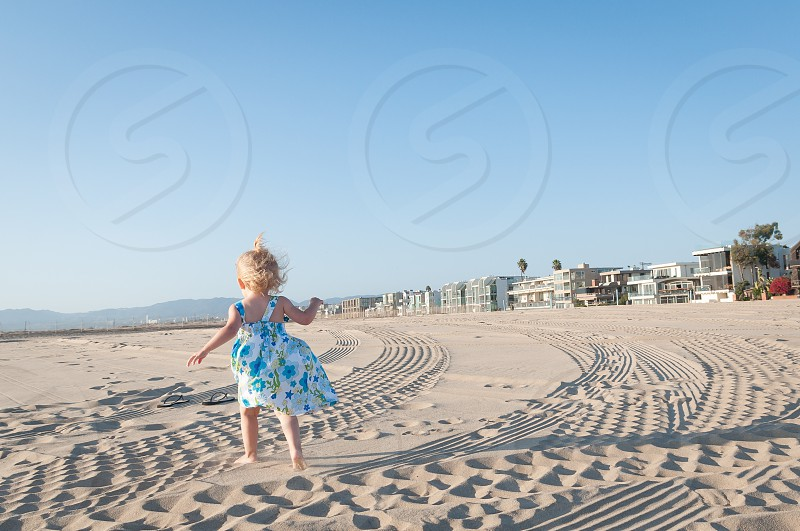 Girl in dress running on the beach photo