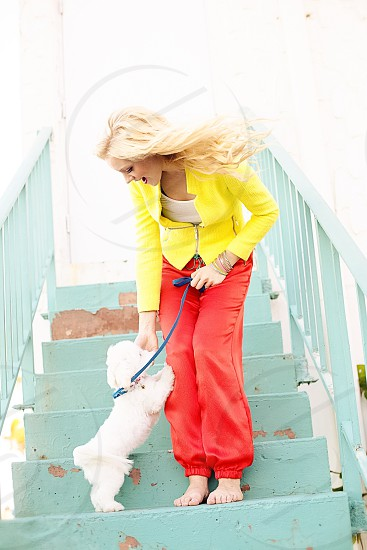 woman in yellow blazer and red pants playing with a white puppy while on stairs during daytime photo