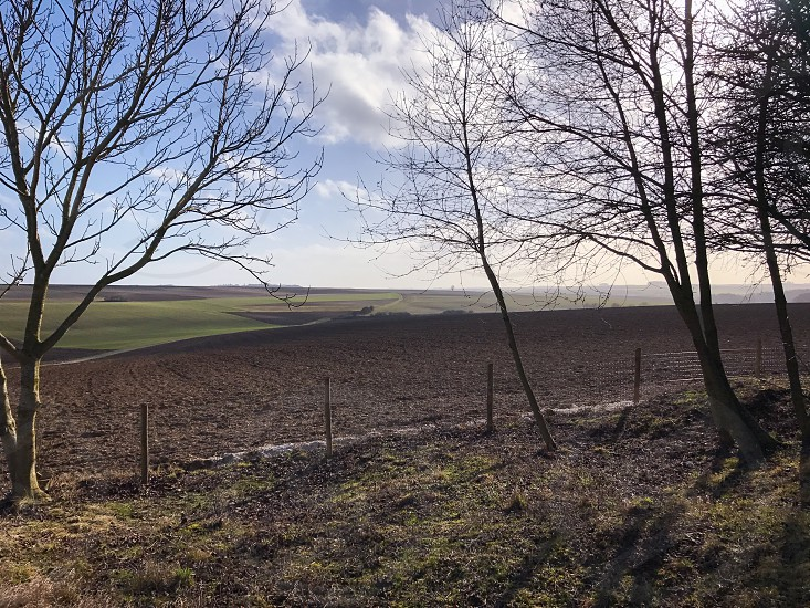Outdoor day landscape horizontal colour La Boiselle France view vista farm farmland fields mud grass trees nature country countryside Europe European mist misty travel fence rustic sky clouds blue winter barren bare photo