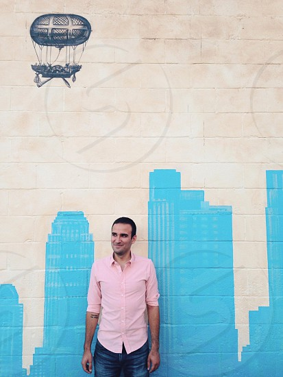 man standing near wall with blue city artwork  photo