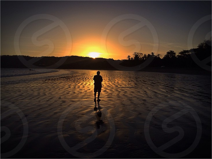 man walking on wet sand with sunset photograph  photo